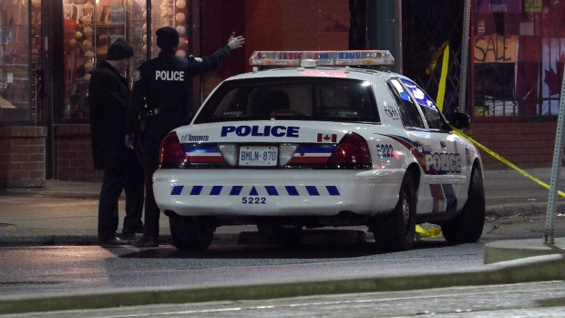 Police investigate the scene of a fatal shooting in downtown Toronto, Sunday, Jan. 31, 2016.