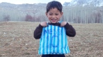 Five-year-old Murtaza Ahmadi was photographed wearing a homemade replica jersey of his favourite player made out of a striped plastic grocery bag and marker, a photo that sparked a social media storm.