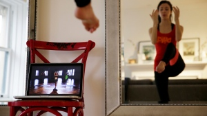Christina Macchiarola demonstrates how she uses the Crunch Live fitness app to work out in her apartment in New York, Apr. 14, 2015. (AP Photo/Seth Wenig)