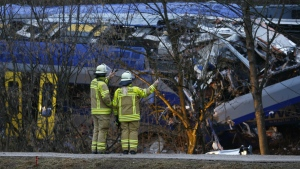 Rescue workers stand in front of two trains that collided head-on near Bad Aibling, Germany, Wednesday, Feb. 10, 2016. (AP / Matthias Schrader)