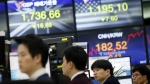 Currency traders look at the computer monitors near the screens showing the foreign exchange rates at the foreign exchange dealing room in Seoul, South Korea, Thursday, Feb. 11, 2016. (AP / Lee Jin-man)