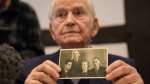 Auschwitz concentration camp survivor Leon Schwarzbaum presents an old photograph showing himself, left, next to his uncle and parents who all died in Auschwitz during a press conference in Detmold, Germany, Wednesday, Feb. 10, 2016. (Bernd Thissen / dpa)