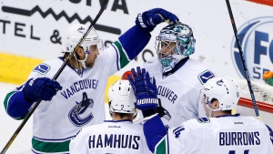Vancouver Canucks' Ryan Miller, top right, celebrates the team's 2-1 win against the Arizona Coyotes with Dan Hamhuis (2), Alex Burrows (14) and Chris Tanev, left, after an NHL hockey game Wednesday, Feb. 10, 2016, in Glendale, Ariz. (AP/Ross D. Franklin)