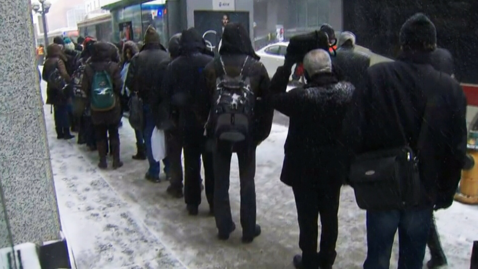 Commuters lineup to board shuttle buses on Bloor Street in Toronto on Tuesday, March 1, 2016.