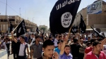 In this June 16, 2014 file photo, demonstrators chant pro-Islamic State group slogans as they carry the group's flags in front of the provincial government headquarters in Mosul, Iraq. (AP / File)