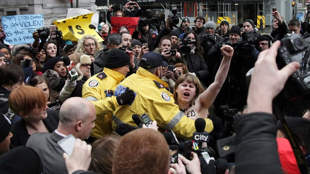 A topless protester gets taken down by police outside of court in Toronto after she interrupted the Crown prosecutor regarding the verdict on former CBC radio host Jian Ghomeshi on Thursday, March 24, 2016. Ghomeshi was acquitted of all charges. THE CANADIAN PRESS/Colin Perkel