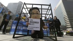 A South Korean university student wearing a mask depicting North Korean leader Kim Jong Un sits in a cage during a rally denouncing North Korea's recent threat for war and human rights situations in Seoul, South Korea on Monday, April 25, 2016. (AP / Ahn Young-joon)