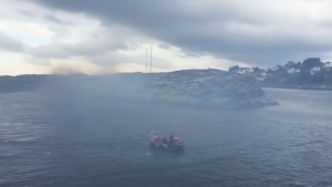 Smoke is seen after a helicopter carrying around 13 people from an offshore oil field crashed Friday near the western Norwegian city of Bergen on Friday, April 29, 2016.