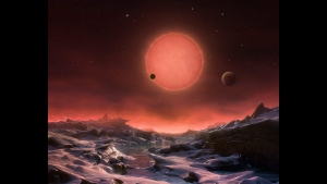 The artist's impression provided by European Southern Observatory on May 2, 2016 shows an imagined view from the surface one of the three planets orbiting an ultracool dwarf star just 40 light-years from earth that were discovered using the TRAPPIST telescope at ESO's La Silla Observatory. (ESO/M. Kornmesser via AP)