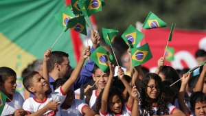 Students wave Brazilian flags during the Olympic torch lighting ceremony at Planalto presidential palace in Brasilia, Brazil, Tuesday, May 3, 2016. The three-month torch relay across Brazil will end at the opening ceremony on Aug. 5 at Maracana stadium in Rio. (AP / Eraldo Peres)