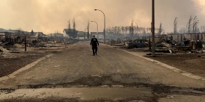 An Alberta RCMP officer surveys the damage on a street in Fort McMurray. (Twitter / @RCMPAlberta)