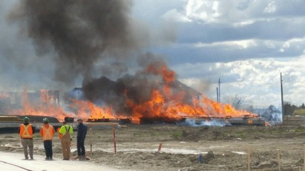 People are seen near a burning housing complex under construction in Brampton on May 5. (Twitter/@Peel_Paramedics)