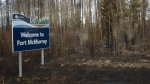 Burned ground surrounds a sign welcoming visitors to Fort McMurray during a media tour of the fire-damaged Alberta city on Monday, May 9, 2016. (Jonathan Hayward / THE CANADIAN PRESS)
