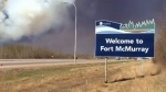 Wildfire smoke blankets the sky behind the 'Welcome to Fort McMurray' sign on May 18, 2016