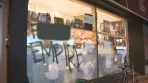 A message in graffiti was written on the window of a high-end Montreal grocery store after 30 masked intruders raided the shop Saturday night. The message reads 'Long live de-gentrification.'