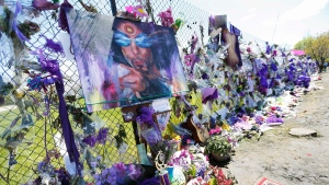 A painting of Prince is displayed on an easel at the flower-covered fence at Paisley Park Studios, Monday, May 2, 2016, in Chanhassen, Minn., where pop rock singer Prince died on April 21. (AP / Jim Mone)