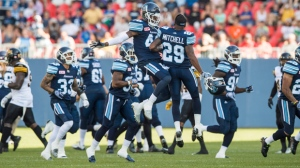 Toronto Argonauts TJ Heath, left, celebrates his interception with teammate Joshua Mitchell during the first half of CFL football preseason action against the Hamilton Tiger-Cats at the first ever CFL football game played at BMO Field, in Toronto, Saturday June 11, 2016. THE CANADIAN PRESS/Mark Blinch