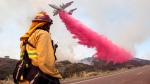Upland Fire Capt. Joe Burna watches as a tanker drops fire retardant to stop a wildfire from jumping over Highway 94 near Potrero, Calif., on Monday, June 20, 2016. (Hayne Palmour IV / San Diego Union-Tribune)