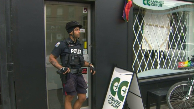 Police are shown outside Cannabis Culture on Queen Street on Thursday afternoon.