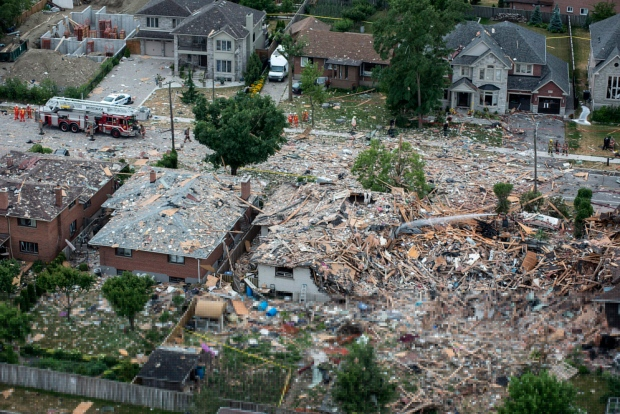Firefighters examine debris after a house explosion in Mississauga, Ont., Tuesday, June 28, 2016. (THE CANADIAN PRESS/Eduardo Lima)