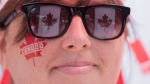 A flag-bespectacled woman smiles as she watches the annual Canada Day parade in Montreal, Friday, July 1, 2016. THE CANADIAN PRESS/Graham Hughes