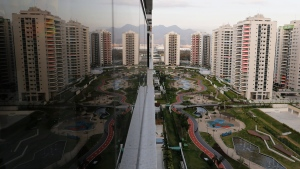 The Olympic Village is reflected in an apartment window in Rio de Janeiro, Brazil, Saturday, July 23, 2016. (AP Photo / Leo Correa)