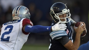Toronto Argonauts' Ricky Ray gets sacked by Montreal Alouettes' Jovon Johnson during first half CFL action in Toronto on Monday, July 25, 2016. (Frank Gunn / THE CANADIAN PRESS)
