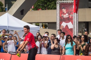 Canadian tennis star Milos Raonic serves the ball to Toronto Mayor John Tory as they hit the court in Nathan Phillips Square to officially kick off the Rogers Cup, in Toronto on Thursday, July 21, 2016. (Aaron Vincent Elkaim / THE CANADIAN PRESS)