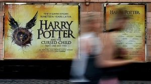 In this photo taken on Thursday, July 28, 2016, pedestrians pass a poster advertising the new Harry Potter play, at the Palace Theatre in London. Nine years after J.K. Rowling's final novel about the boy wizard, Harry has returned, on the stage and the page - and he's still producing commercial alchemy. (AP Photo/Kirsty Wigglesworth)