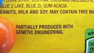 """This April 8, 2016 file photo shows a new disclosure statement which reads, """"PARTIALLY PRODUCED WITH GENETIC ENGINEERING"""" on a package of candy in Montpelier, Vt. (AP / Lisa Rathke)"""