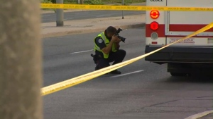 A police collision investigator photographs a TTC bus that was involved in a crash that killed a male pedestrian in Scarborough on July 29. (CP24)