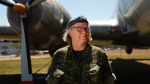 Master Cpl. Natalie Murray, who works at the instrument flight rules control centre at CFB Comox, poses for a photograph beside the Canadair CL-28 Argus Mark 1 at Heritage Air Park near the base in Comox, B.C., Friday, July 29, 2016. (Chad Hipolito/The Canadian Press)