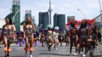 Mas band members walk around after going through the judging area during the Toronto Caribbean Carnival's grand parade, in Toronto on Saturday, July 30, 2016. (Cole Burston / THE CANADIAN PRESS)