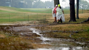 Women walk by the 18th hole after third round play was suspend for the day at the PGA Championship golf tournament at Baltusrol Golf Club in Springfield, N.J., Saturday, July 30, 2016. (Tony Gutierrez/AP Photo)