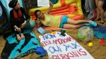 "Activists protest outside the French embassy, during the ""wear what you want beach party"" in London, Thursday, Aug. 25, 2016. (AP / Frank Augstein)"