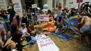 Activists protest outside the French embassy, during the 'wear what you want beach party' in London on Thursday, Aug. 25, 2016. (AP / Frank Augstein)