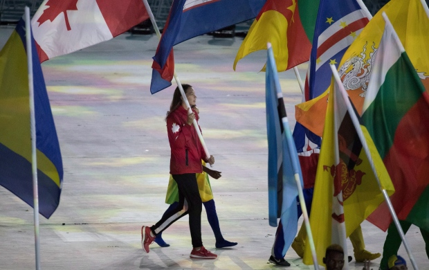 Penny Oleksiak carries the Canadian flag into the closing ceremonies of the Olympic games in Rio de Janeiro, Brazil, Sunday, August 21, 2016.