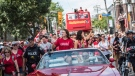 Canada's Olympic team flag-bearer and gold medalist Penny Oleksiak, centre left, and fellow swim team member Michelle Williams ride in the back of a prade car for an Olympic parade celebration in Toronto on Sunday August 28, 2016. THE CANADIAN PRESS/Aaron Vincent Elkaim