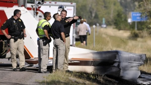 "Missoula County sheriff's deputies look at the wreckage of a Cessna 182 that crashed on the shoulder of Interstate 90 near Rock Creekont., on Sunday, Aug. 28, 2016. The crash killed 52-year-old Darrell Ward of Deer Lodge, a star of the History channel series ""Ice Road Truckers"" and pilot Mark Melotz, 56, of Arlee. (Tom Bauer/The Missoulian)"