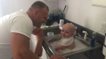 "Trooper Derek Graham, a father of four, said the ""dad instinct"" took over when he removed the baby's soiled diaper, put him in a sink and began to bathe him. (Source: Derek Graham, West Virginia State Police)"