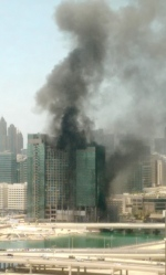 In this photo provided by Hasan Qureshi, smoke rises from a blaze that broke out in a high-rise building under construction in Abu Dhabi, United Arab Emirates, Tuesday, Aug 30, 2016. (Hasan Qureshi via AP)