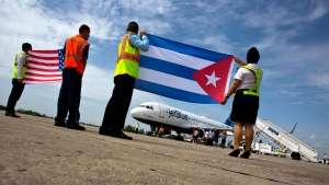 Airport workers receive the JetBlue flight 387 holding a United States, and Cuban national flag, on the airport tarmac in Santa Clara, Cuba, Wednesday, Aug. 31, 2016. (AP Photo/Ramon Espinosa)