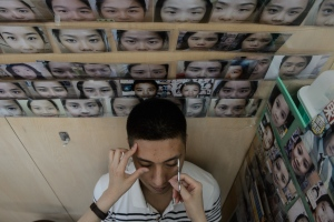 In this picture taken on July 22, 2016, customer Edward Lam, a 35-year-year old technician for a television station, has his eyebrows plucked by trained face reader Li Chau-jing, who makes slight changes to her client's brows to bring them better luck.
