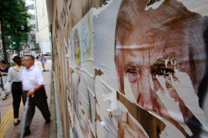 People walk past posters of U.S. presidential candidate Donald Trump in Tokyo, Thursday, Sept. 29, 2016. Trump's ambiguous answer to a debate question on nuclear restraint raised doubts about his understanding of the issue. (AP / Shizuo Kambayashi)