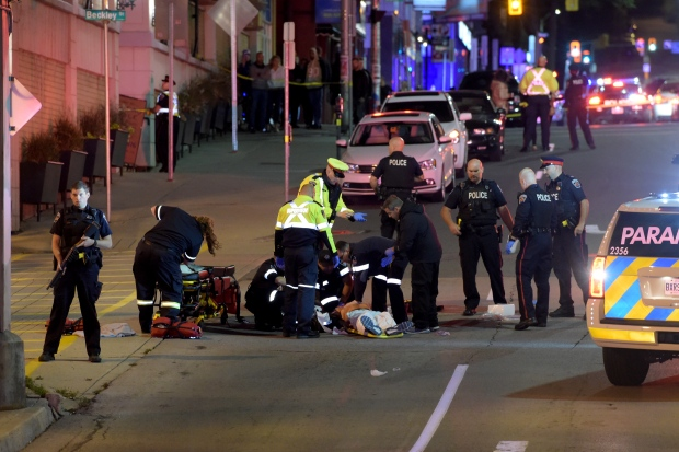 Emergency crews treat a victim following a police-involved shooting in Hamilton late Friday night. (Andrew Collins)