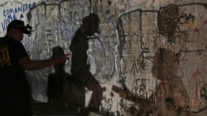 The shadows of police investigators are reflected on a wall as they check an unidentified body of an alleged drug lord after it was dumped along a dark alley in Manila, Philippines on Sept. 21, 2016. (AP / Aaron Favila)