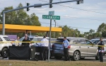 The body of former NFL player Joe McKnight lies between the shooter's vehicle at left and his Audi SUV at right as the Jefferson Parish Sheriff's Office investigates the scene in Terrytown, La., Thursday, Dec. 1, 2016. (Michael DeMocker / NOLA.com The Times-Picayune via AP)