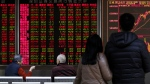 Investors chat near an electronic board displaying Shenzhen trading stock prices at a brokerage house in Beijing, Monday, Dec. 5, 2016. (AP / Andy Wong)