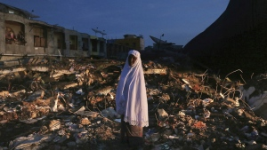 A woman stands on the ruin of a market after Wednesday's earthquake in Meureudu, Aceh province, Indonesia, early Thursday, Dec. 8, 2016. (AP / Heri Juanda)
