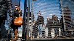 Pedestrians pass through tall security fencing erected around the National Mall in Washington, Wednesday, Jan. 18, 2017, as preparations continue for Friday's presidential inauguration. (AP Photo/John Minchillo)